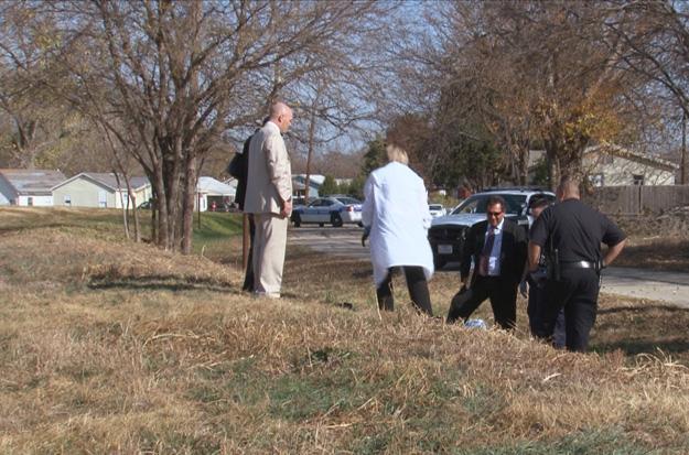 Detective Sayers examines victim's gunshot wounds