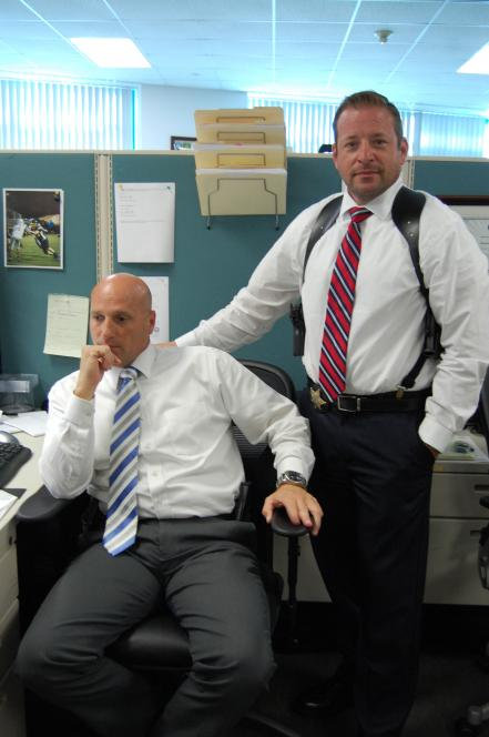 Detective Forsberg watches Perez demonstrate shoulder holster