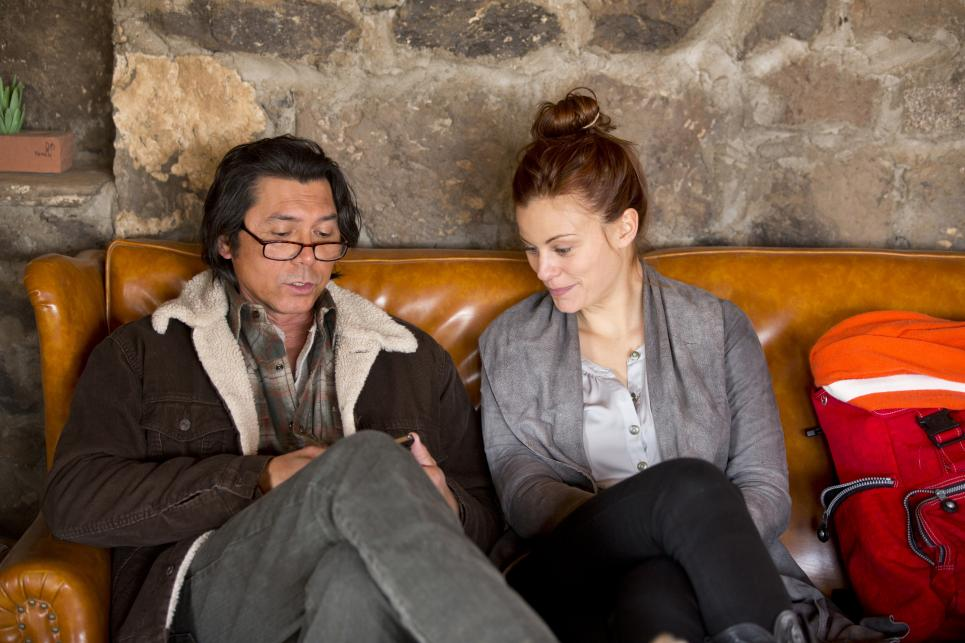 Lou Diamond Phillips shows Cassidy Freeman something on his phone