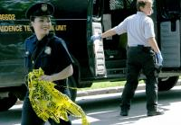 Officer collects police tape