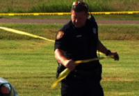 Officer marks area with police tape