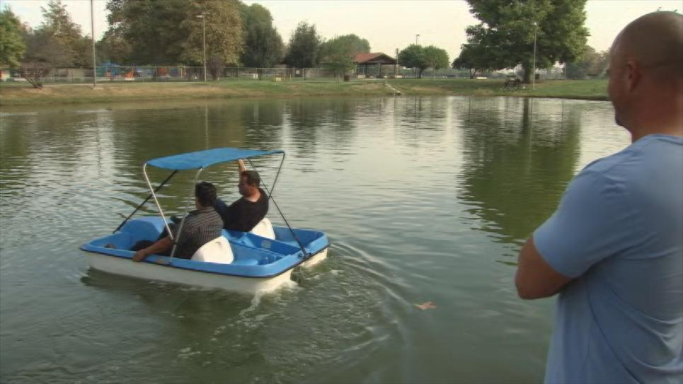 Antonio shows his paddle boat to Alex