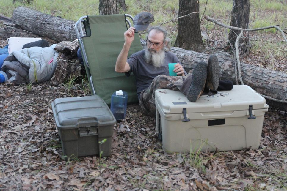 Si relaxes at campsite with iced tea