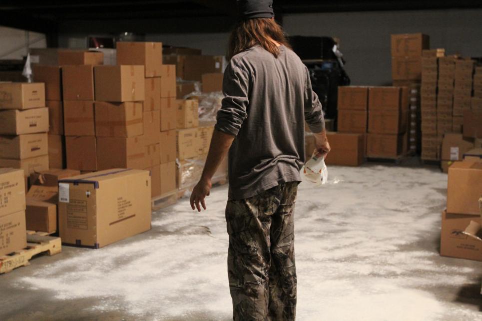 Jase sprinkles flour on warehouse floor