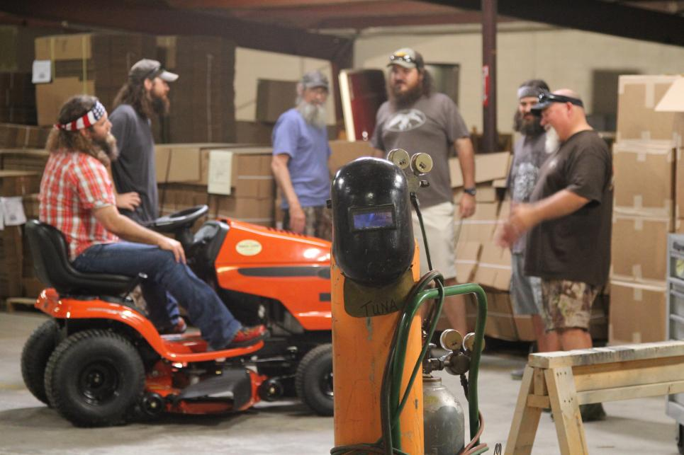 Employees discuss how to soup up lawn mower