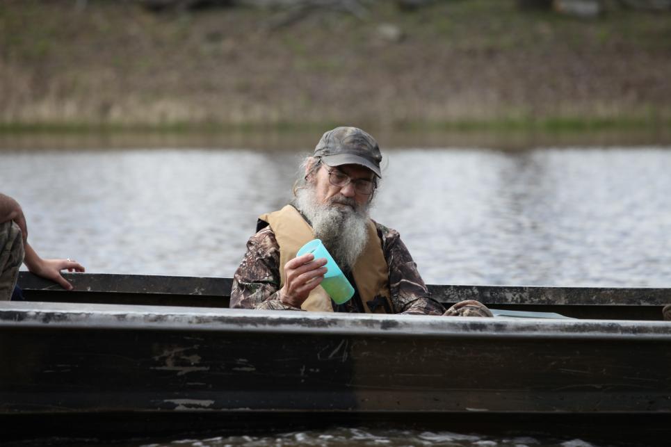 Si Robertson drinks iced tea on boat