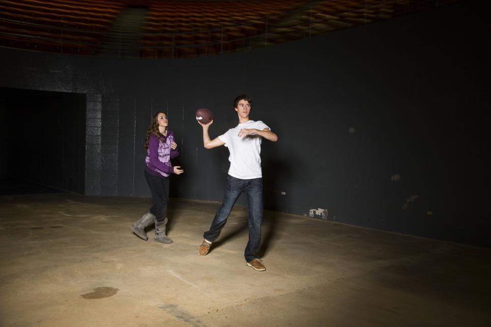 Sadie and John toss football at camo shoot