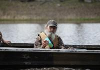 Si Robertson drinks iced tea on boat