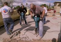 Volunteers jackhammer driveway