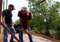 Roy uses planks to unload water tower