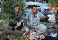 Longworth watches Sanchez examine body