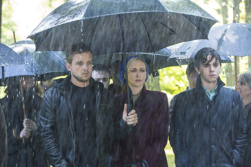 Dylan, Norma, and Norman stand in the rain at Miss Watson's funeral