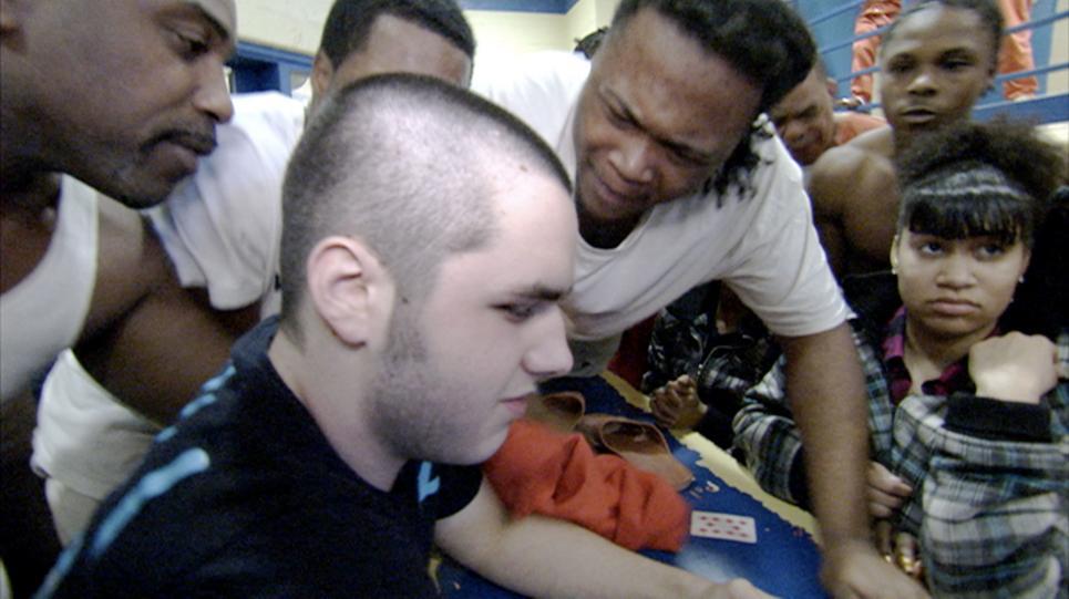 Inmates surround Dylan.