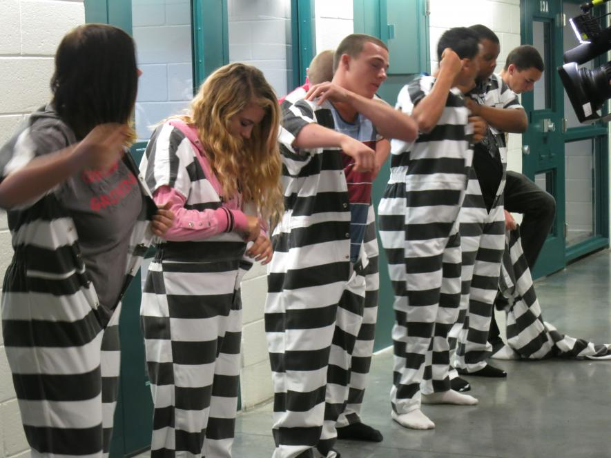 The teens change into jail jumpsuits.
