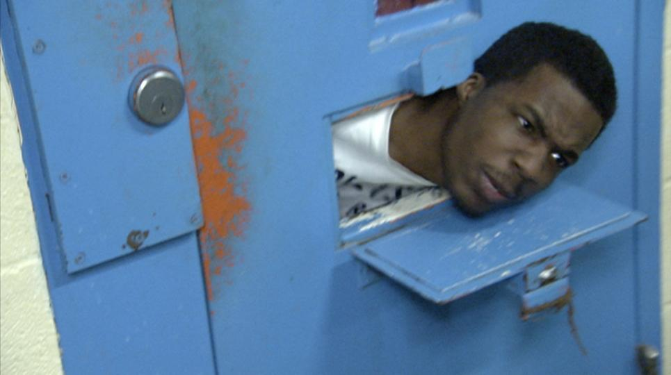 An inmate sticks his head through his cell door.