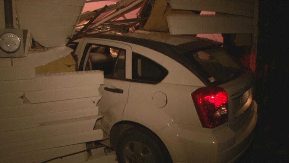 Police find a car has crashed into the woman's house.