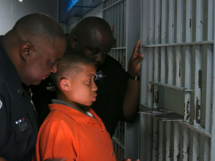 A teen looks at the dark cells inmates occupy
