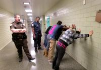 The teens face the wall and assume the position.