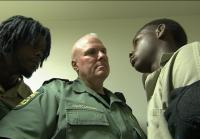 A deputy holds back an inmate