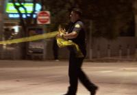 Officer marks area with crime scene tape