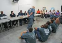 Teens sit before  inmates as parents watch